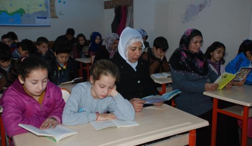 Öğrenci, öğretmen ve veli birlikte kitap okuyor